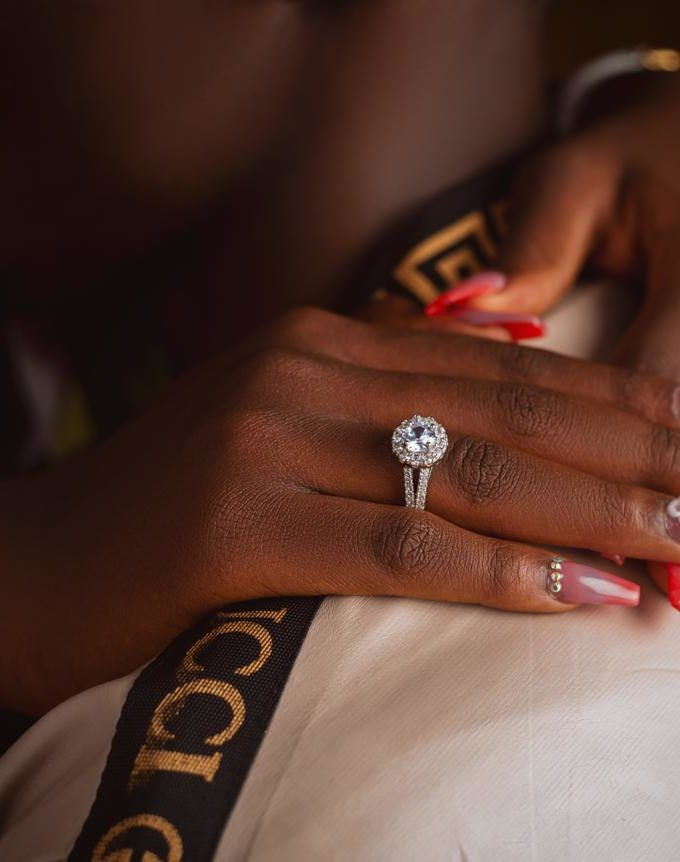 A ring on the finger of a lady whose hands are placed on the shoulder of a man the ring is used for engagement and wedding